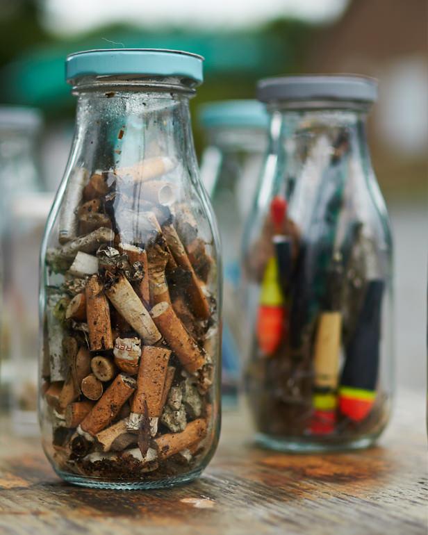 Zwei Gläser gefüllt mit alten Zigarettenstummeln und Feuerzeugen