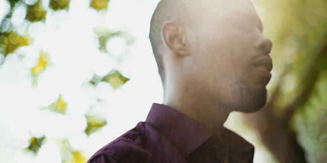 Mensch mit geschlossenen Augen vor unscahrfen Hintergrund. Sonne fällt ihm ins Gesicht