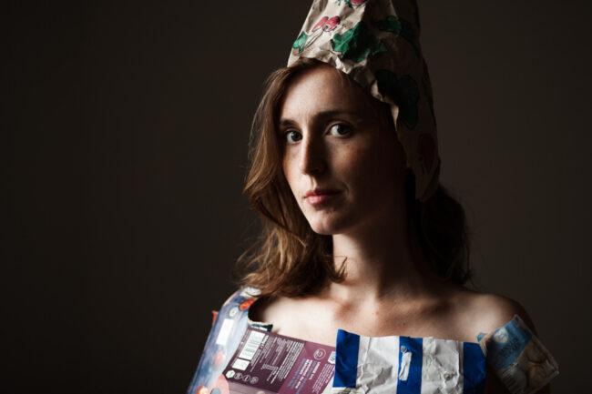 Ein nahes Portrait einer Frau, die mit Müll bekleidet ist.