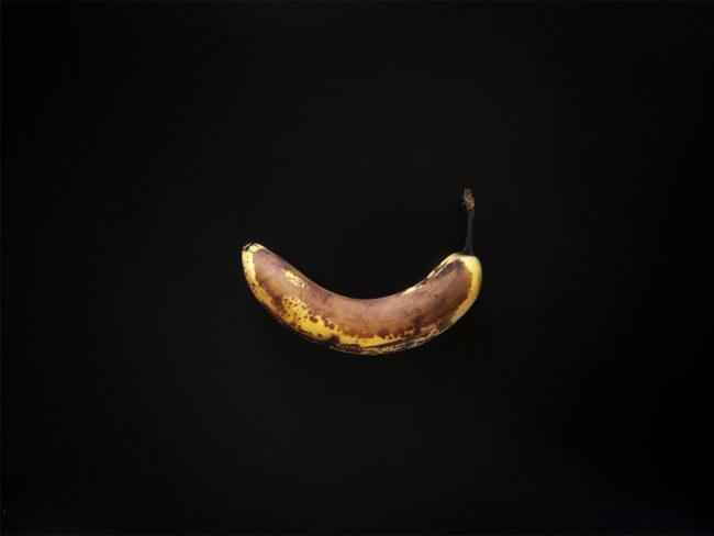 Banane mit braunen Stellen auf einem schwarzen Hintergrund