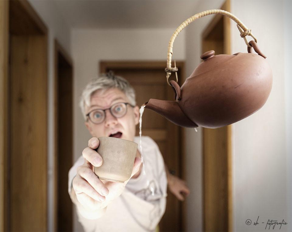 Eine Person hält mit erschrockendem Gesicht eine Tasse vor eine schwebende Teekanne. Der Tee läuft daneben.