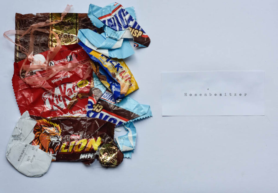 """Verpackungsmüll von Süßigkeiten auf der linken Bildhälfte, rechts daneben ein zettel mit der Aufschrift """"Hosenbesitzer"""""""