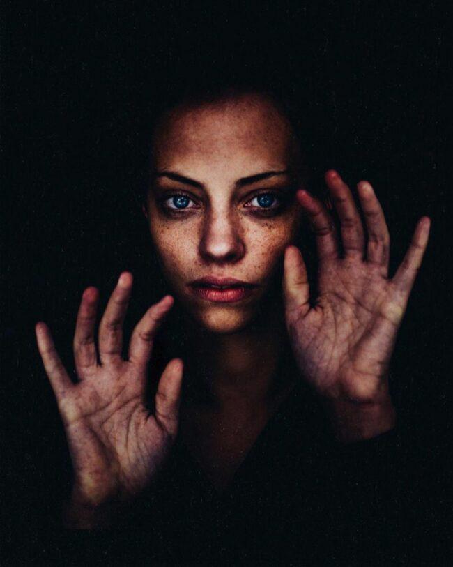 Frau hält zwei Hände offen neben ihren Kopf