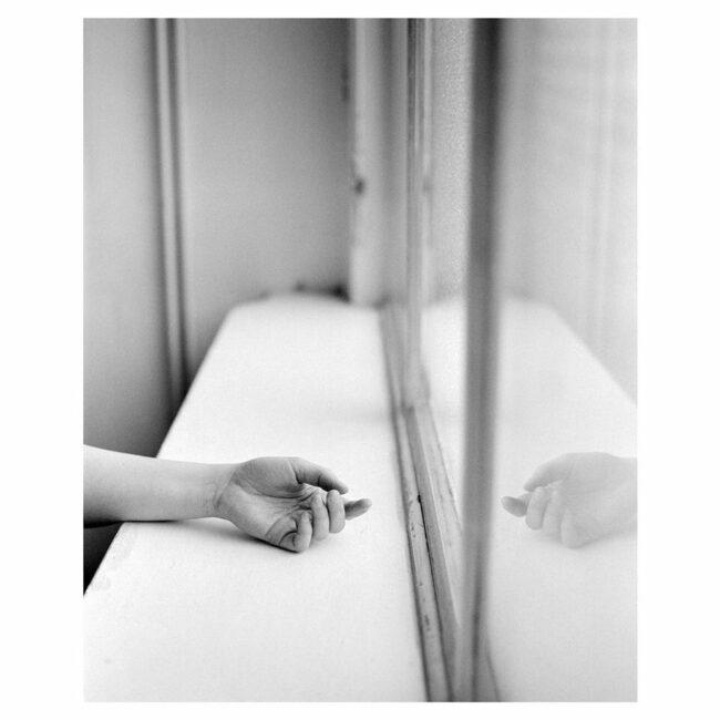 Eine Hand liegt auf einem Fenstersims und spiegelt sich in der Scheibe