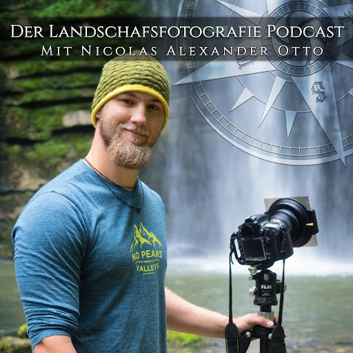Mann steht mit Kamera vor einem Wasserfall