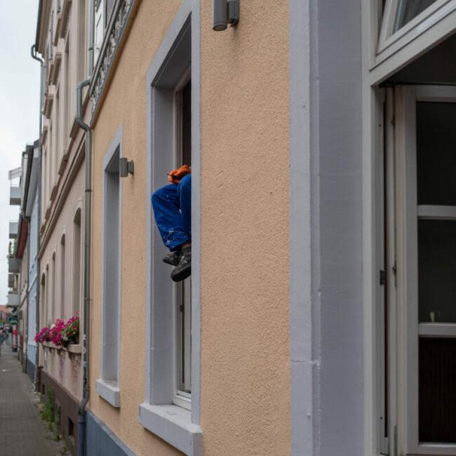 In einem Fensterrahmen seitlich aufgenommen scheint eine Person im Schneidersitz zu schweben.