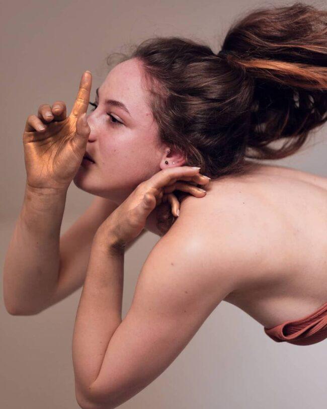 Eine Frau posiert dramatisch mit ihren Händen, die golden angemalt sind