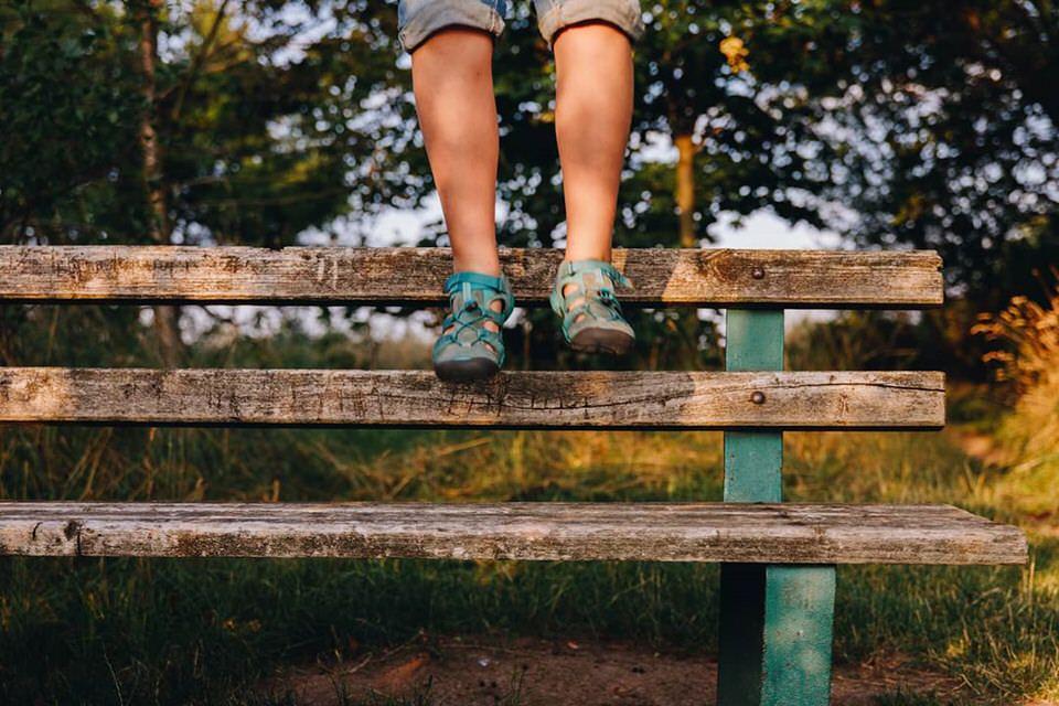 Kinderbeine springen von einer Bank