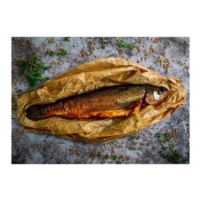 Gebratener Fisch angerichtet auf braunem Papier