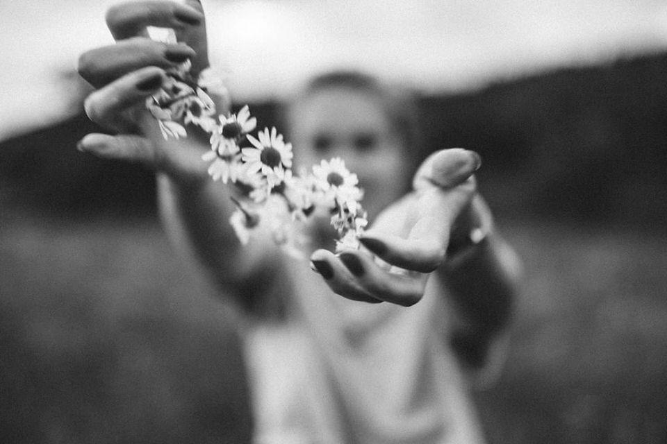 Hände reichen einen Kranz aus Gänseblümchen