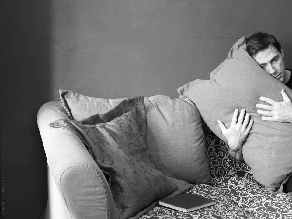 Ein Mann auf einem Sofa hält die Hände um ein Kissen geklammert