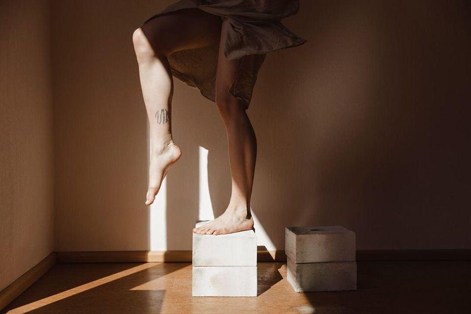 Zwei Beine, die auf einem Stein nach oben steigen, vom Licht beschienen