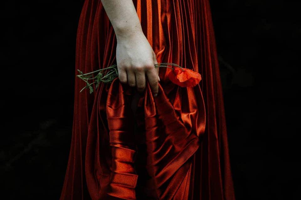 Eine Person in in rotem Kleid hält eine Mohnblume in der Hand