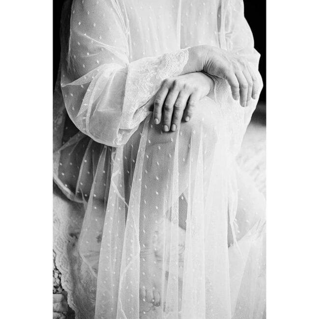 Eine Person hält zwei Arme verschrenkt vor ihrem weißen Kleid