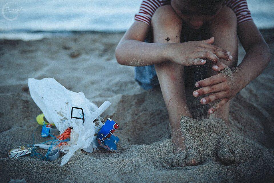 Ein Kind sitzt im Strand, neben ihm liegt ein Haufen Müll