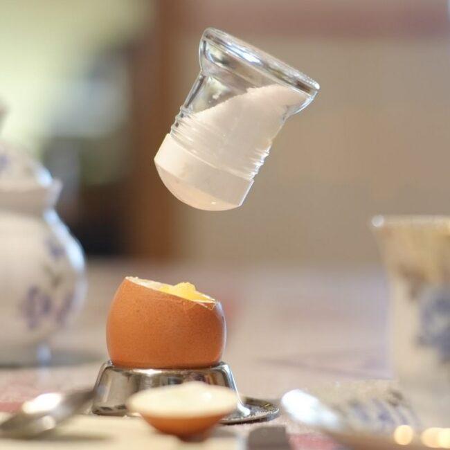 Ein schwebender Salzstreuer über einem Ei