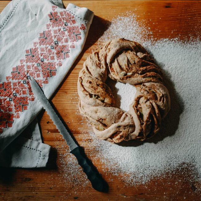 Brotzopf liegt im Mehl, ein Messer und ein Tuch liegen daneben