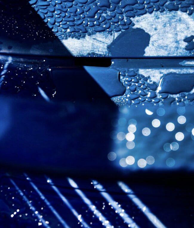 Surreales Bild: Wassertropen auf blauer Oberfläche