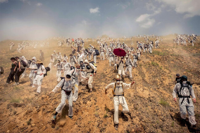 Menschen in schutzanzügen rennen einen Sandhügel hinunter
