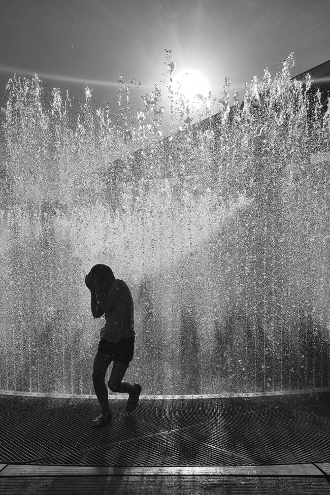 Ein Kind rennt mit schützendem Armen nach oben vor einem Springbrunnen