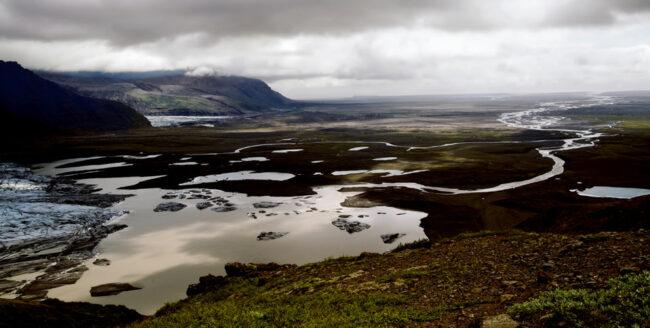 Landschaft mit Gewässer und Bergen vor Wolken