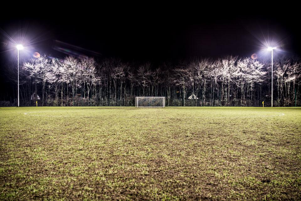 Leeres Fußballfeld nachts mit Blick zum Tor
