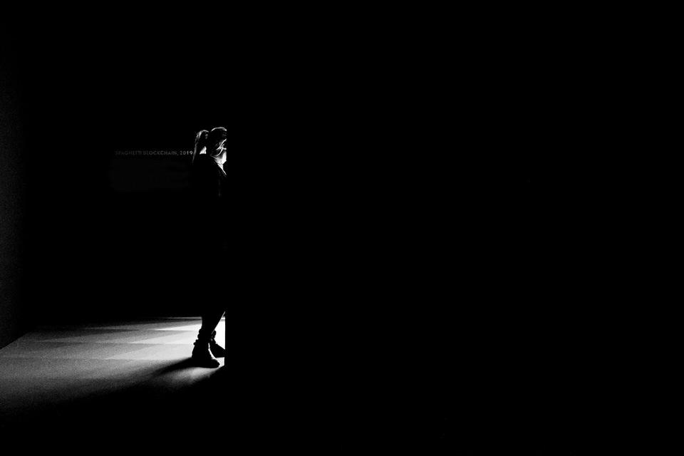 Eine Person geht von einem dunklen Raum in einen voller Licht