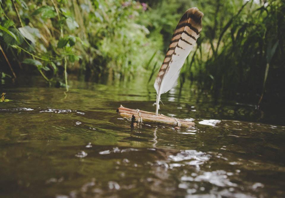 Ein kleines Spielzeugflos auf einem Wasser. Eine Feder dient als Segel.