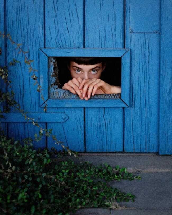 Eine Person schaut durch eine Katzenklappe