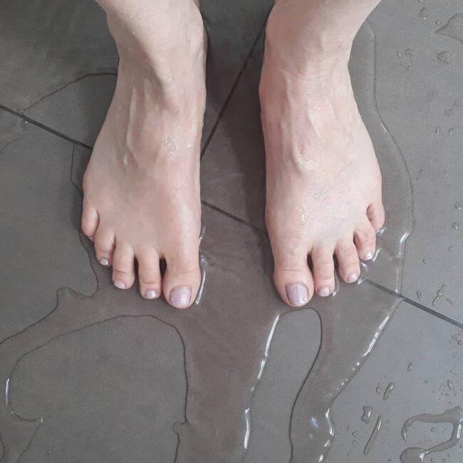 Zwei Füße in einer Pfütze Wasser auf Fliesenboden