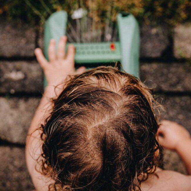 Vogelperspektive: Ein nasser Kinderkopf vor einem Rasensprenger