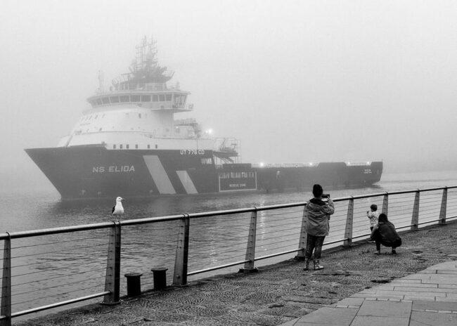Kinder stehen an einer Brüstung mit Blick auf ein großes Schiff