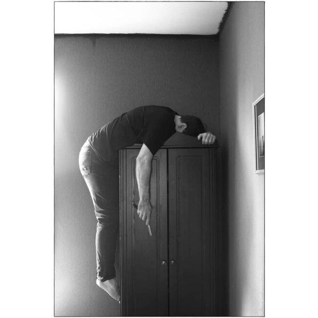 Eine Person liegt hängt5 auf einem Kleiderschrank