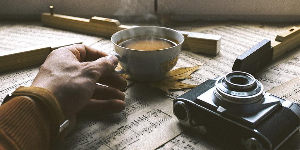 Eine Hand hält eine Tasse heißen Kaffee, die auf einem Schreibtisch voller Notenblätter steht. Daneben liegt eine Kamera.
