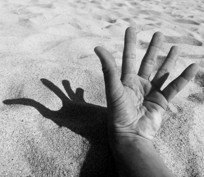 Eine Hand wirft einen Schatten in den Sand