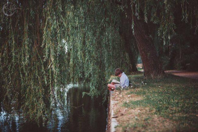Junge sitzt am Ufer vor einer Trauerweide