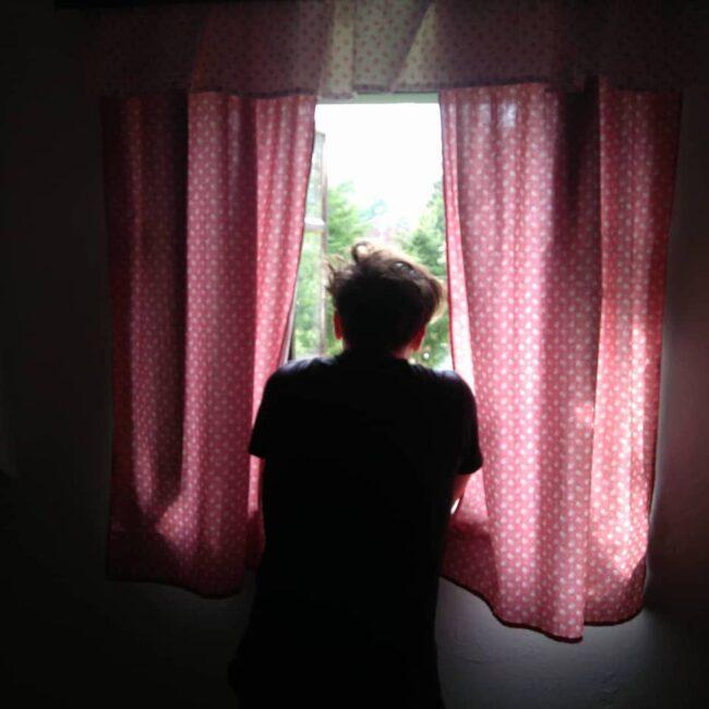 Eine Person schaut zum Fenster hinaus