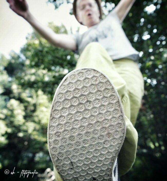 Person tritt scheinbar mit Schuh auf die Kamera