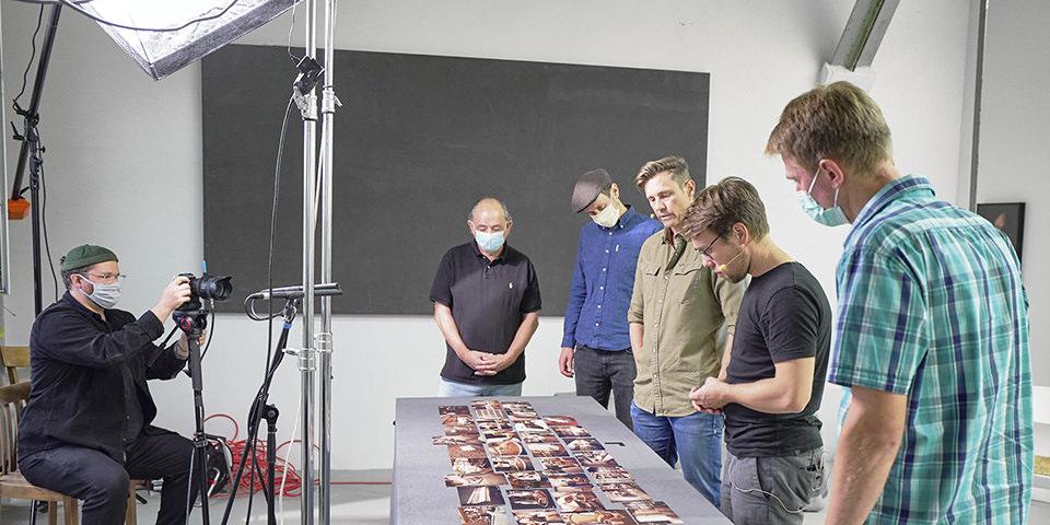 Menschen stehen um einen Tisch mit Bildern
