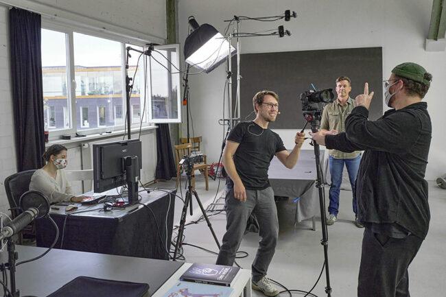 Ein Mann steht lachend vor einer Kamera