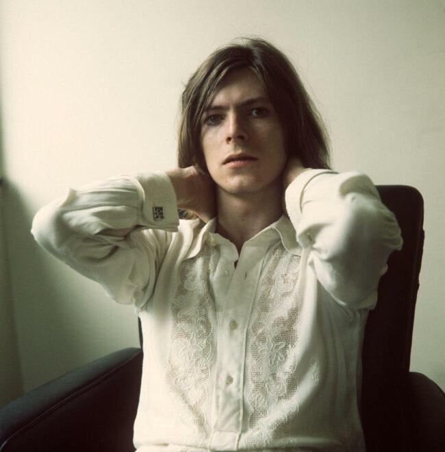 Portrait von David Bowie in weißem Hemd und mit langen Haaren. Er hält beide Hände in den Nacken.