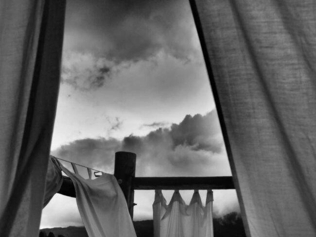 Gardinen vor wolkenbehangenem Himmel