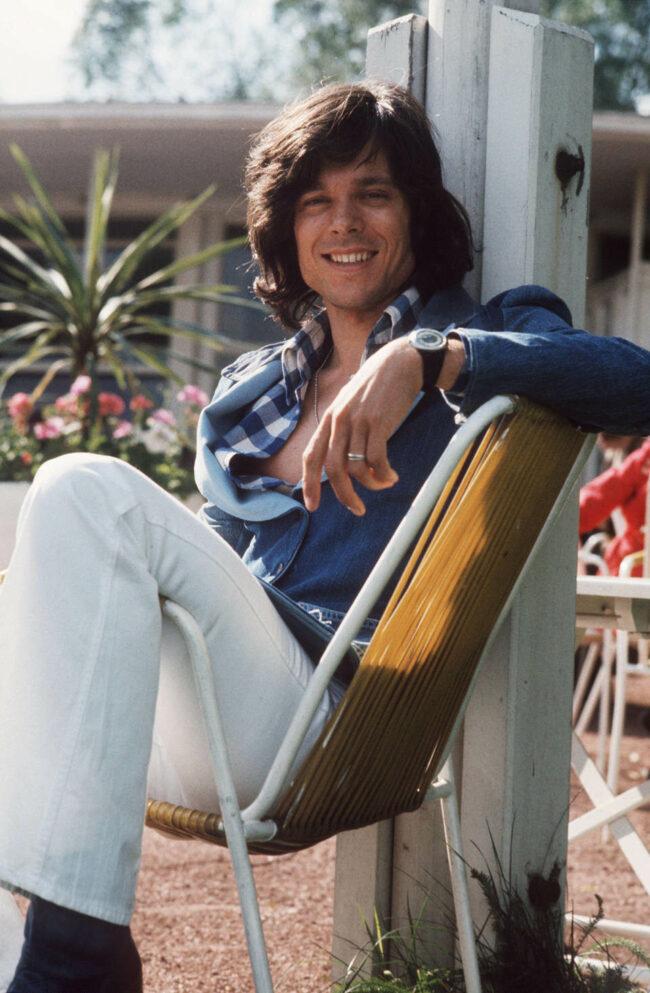 Portrait von Jürgen Drews, der lächelnd auf einem Stuhl sitzt.