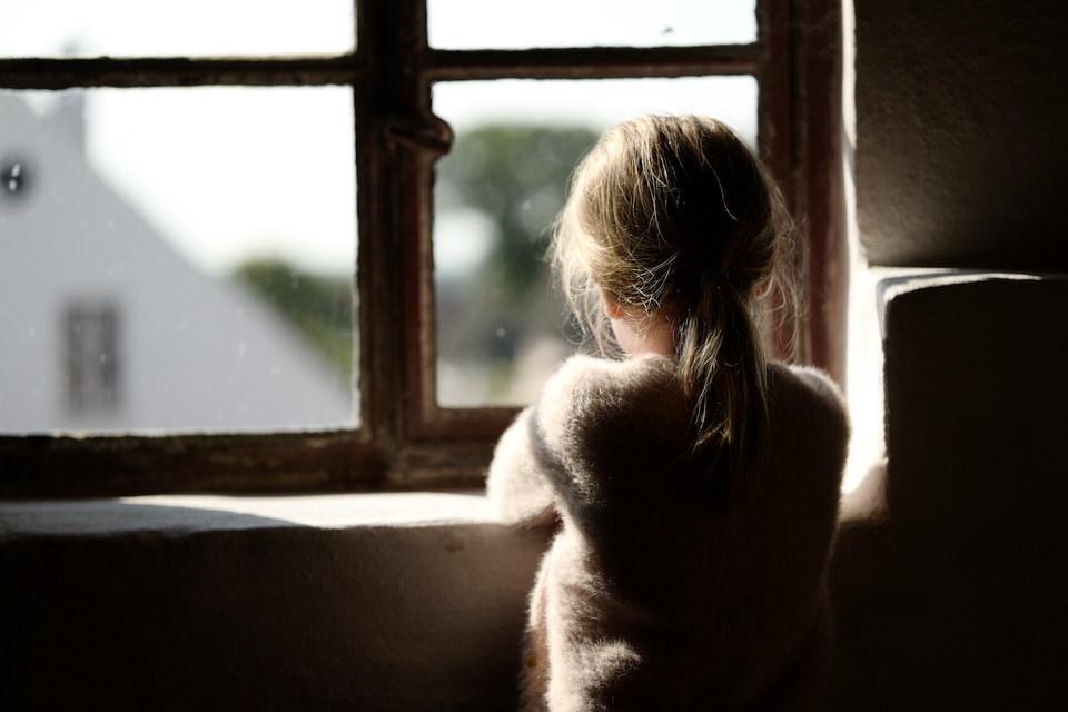 Kind sieht aus dem Fenster