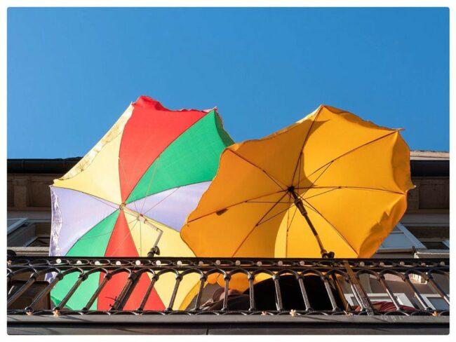 Zwei Sonnenschirme auf einem Balkon von unten