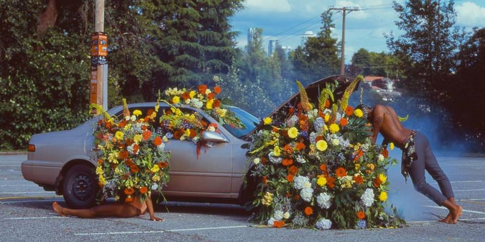 Ein mit Blüten gefülltes Auto auf einem Parkplatz.