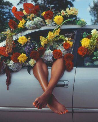 Überschlagene Beine ragen aus einem Autofenster, das mit Blüten gefüllt ist.