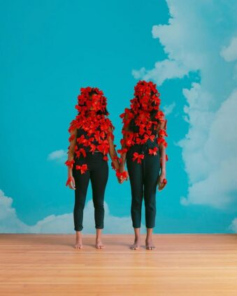 Zwei mit roten Schleifen überdeckte Personen stehen vor einem blauen Himmel.