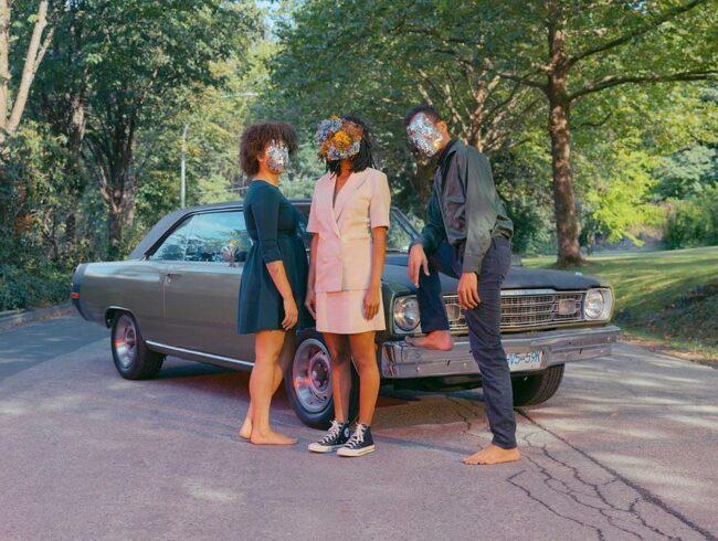 Drei Personen stehen auf einer Straße vor einem Auto.