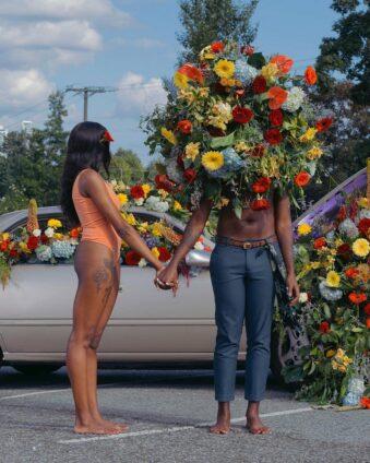 Zwei Personen halten sich an den Händen und stehen auf einem Parkplatz vor einem mit Blüten gefüllten Auto.